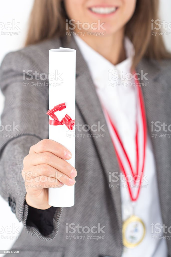 Young Businesswoman holds up her certificate, gold medal around her neck stock photo