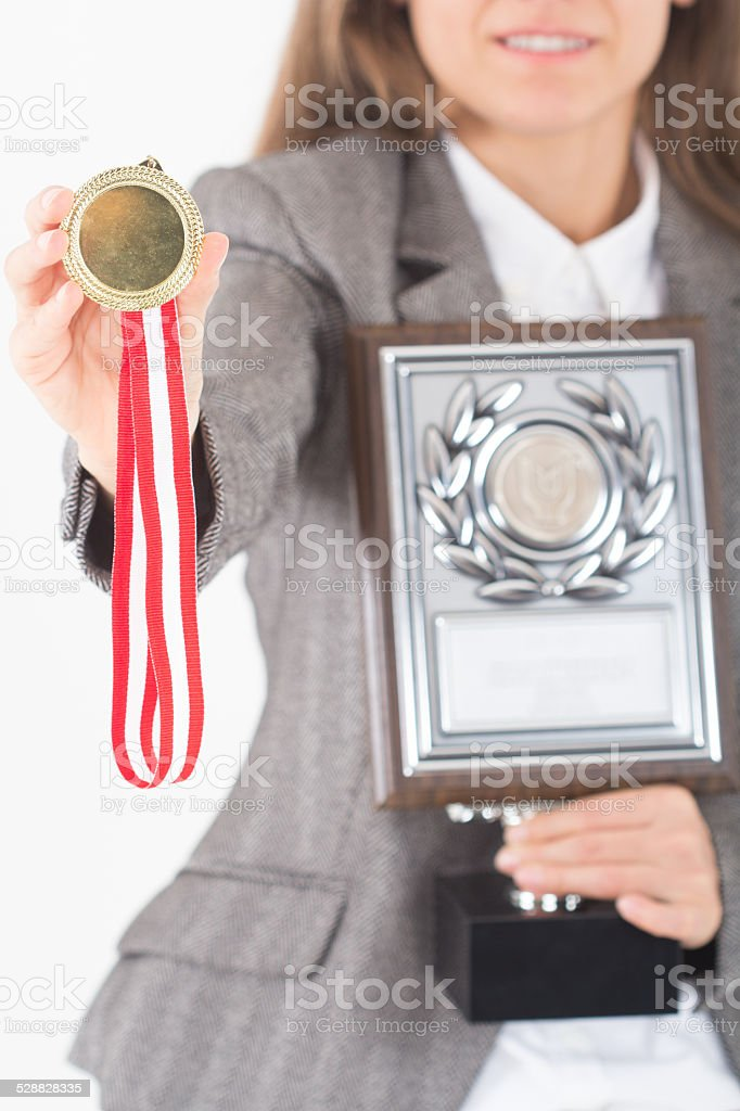 Young Businesswoman holds up her gold medal and awar stock photo
