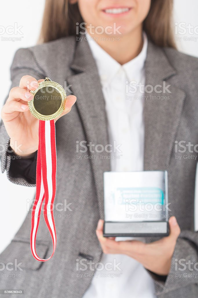 Young Businesswoman holds up her gold medal and award stock photo