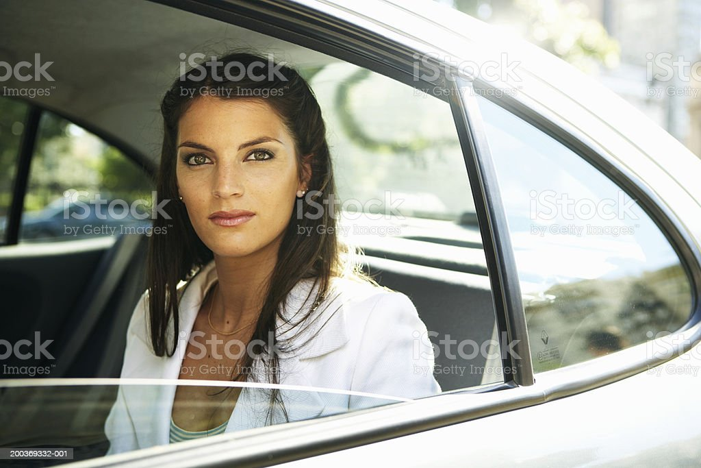 Young businesswoman in back seat of car, portrait stock photo