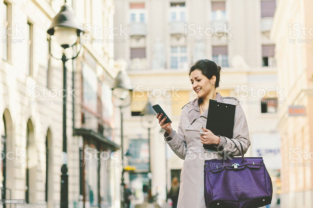 Young businesswoman in the city using smart phone stock photo