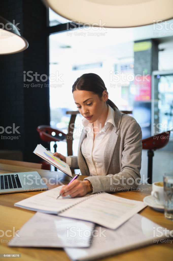 Young businesswoman in the office brainstorming over business report. stock photo