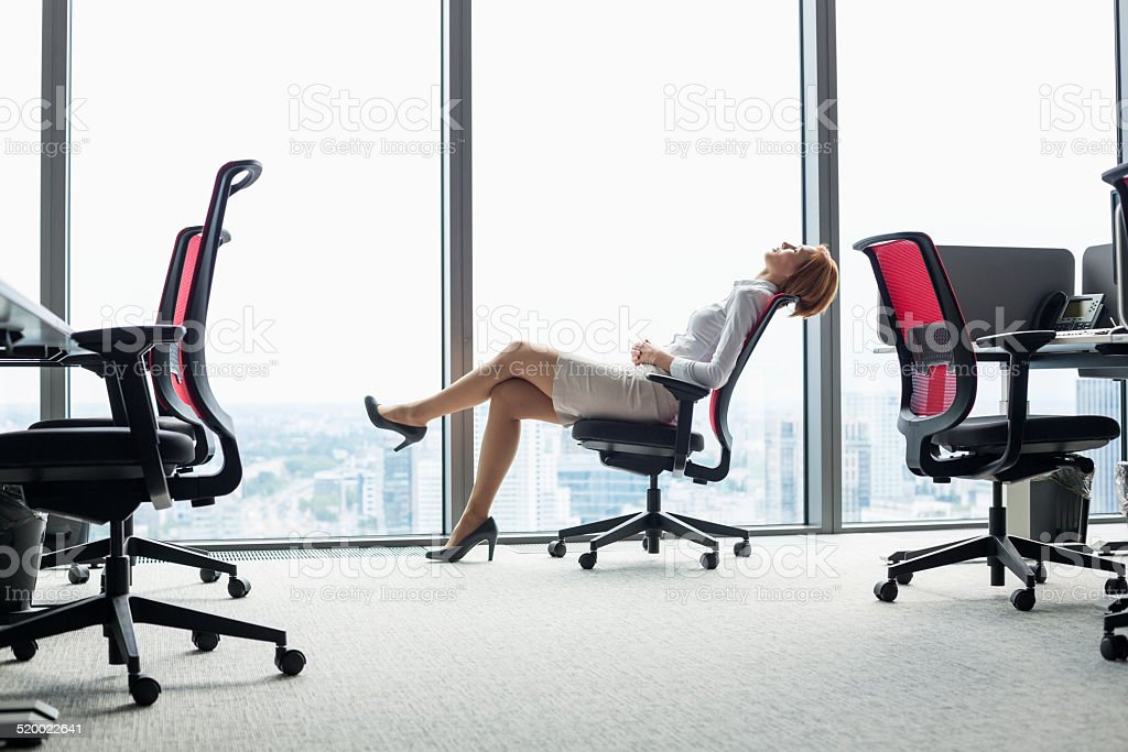 Young businesswoman leaning back in chair at office stock photo