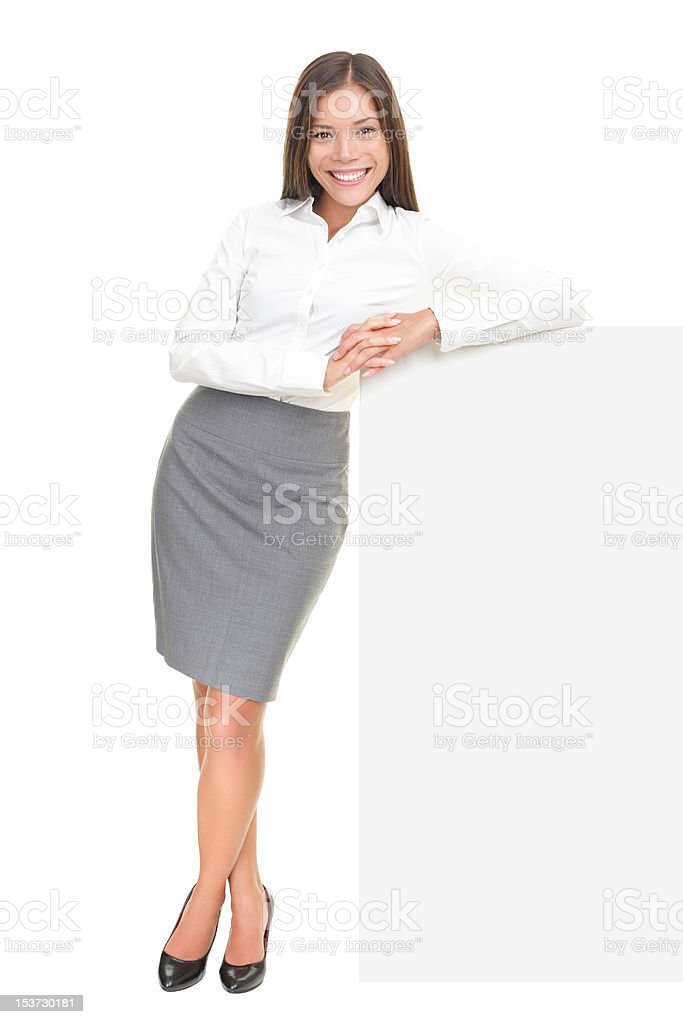Young businesswoman leaning on sign stock photo