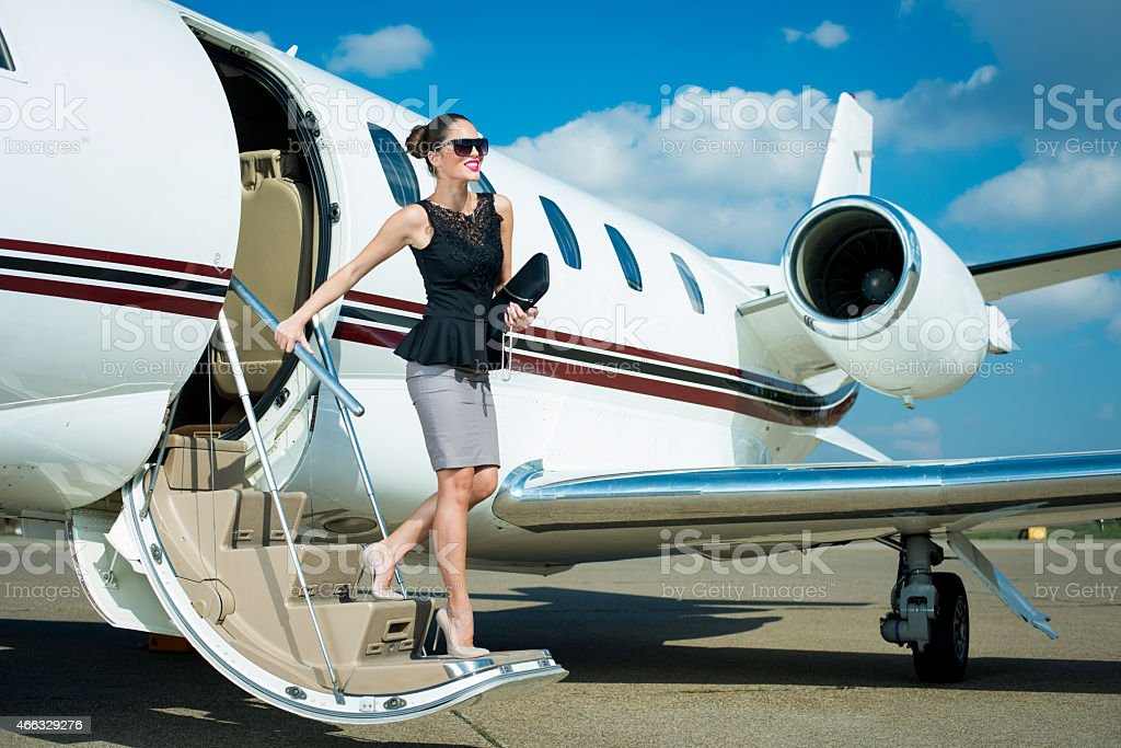 Young businesswoman leaving private jet airplane stock photo