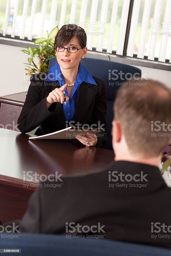 Young Businesswoman Lecturing a Businessman at Desk in Office stock photo