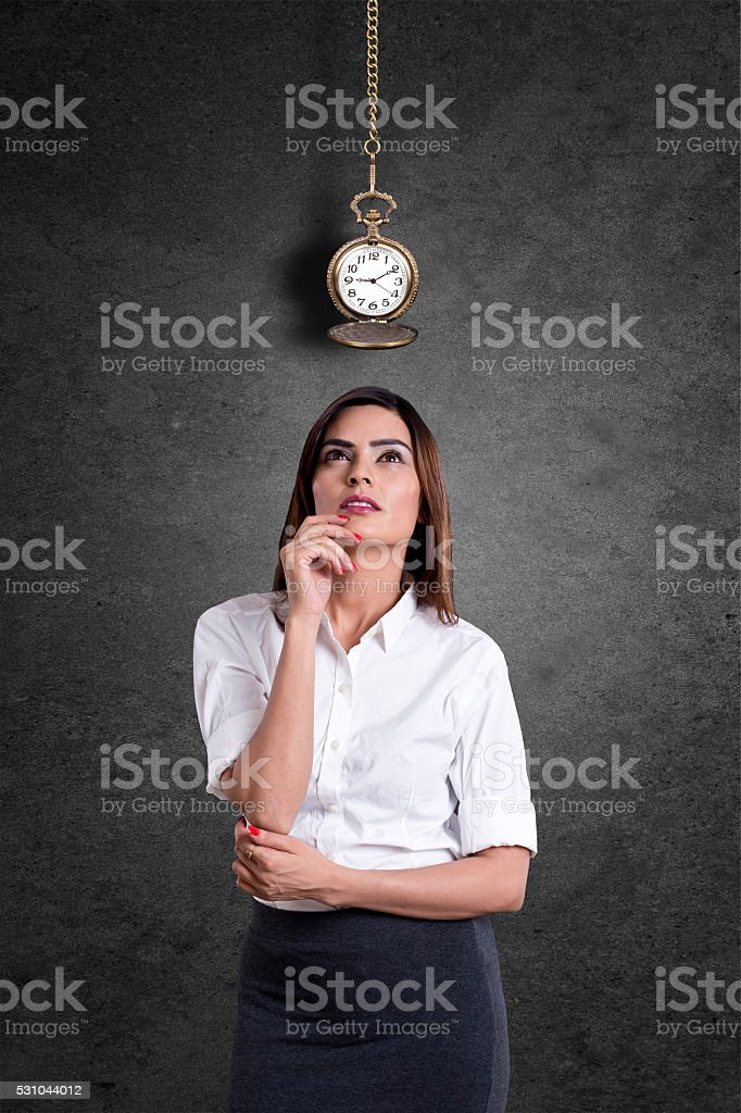 Young businesswoman looking at pocket watch stock photo