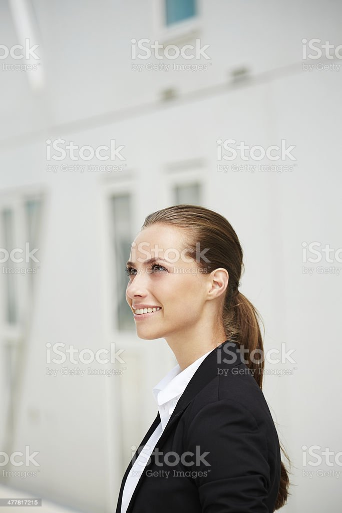 Young businesswoman looking up and smiling royalty-free stock photo