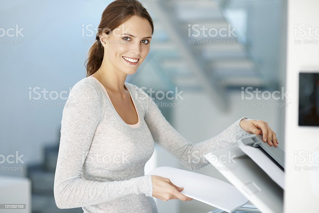 Young businesswoman making copies on the photocopy machine stock photo