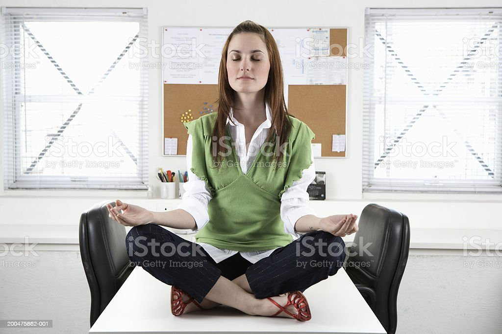 Young businesswoman meditating atop desk, eyes closed stock photo