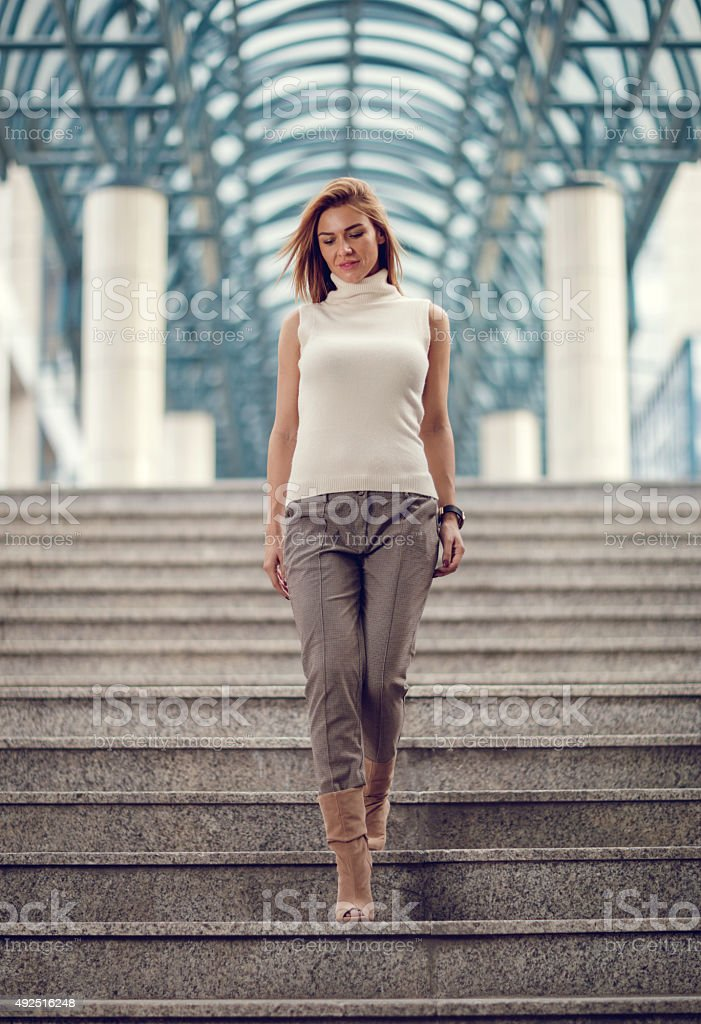 Young businesswoman moving down the stairs. stock photo