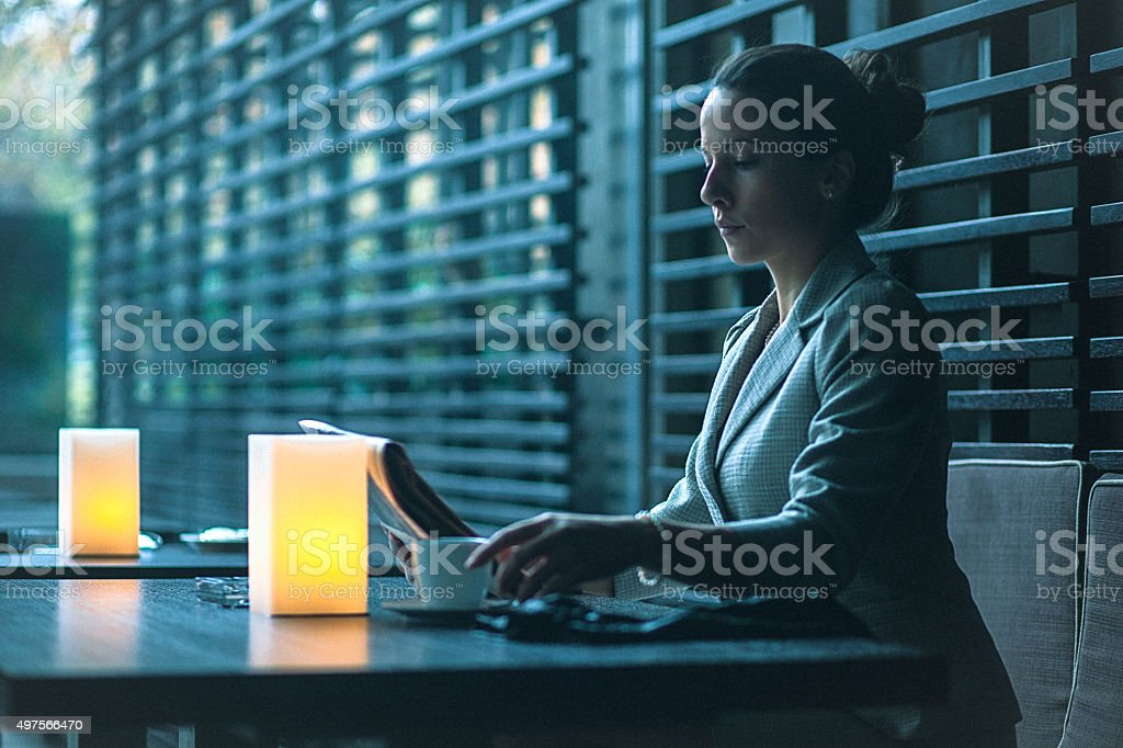 Young businesswoman on coffee break at cafe, reading newspaper stock photo