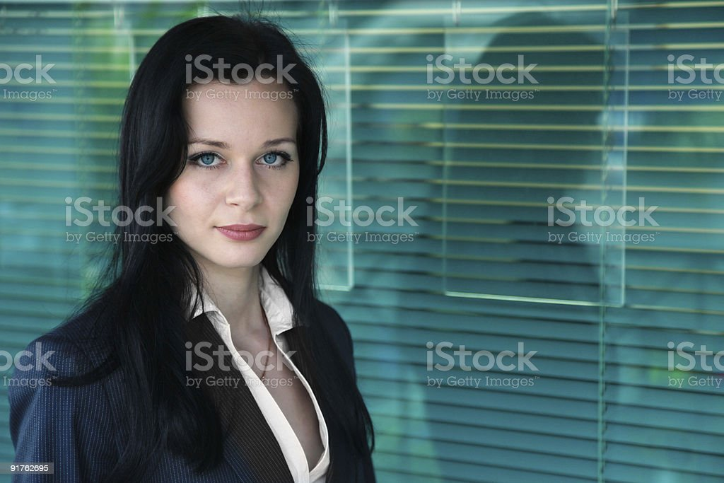 Young Businesswoman on turquoise office window background royalty-free stock photo