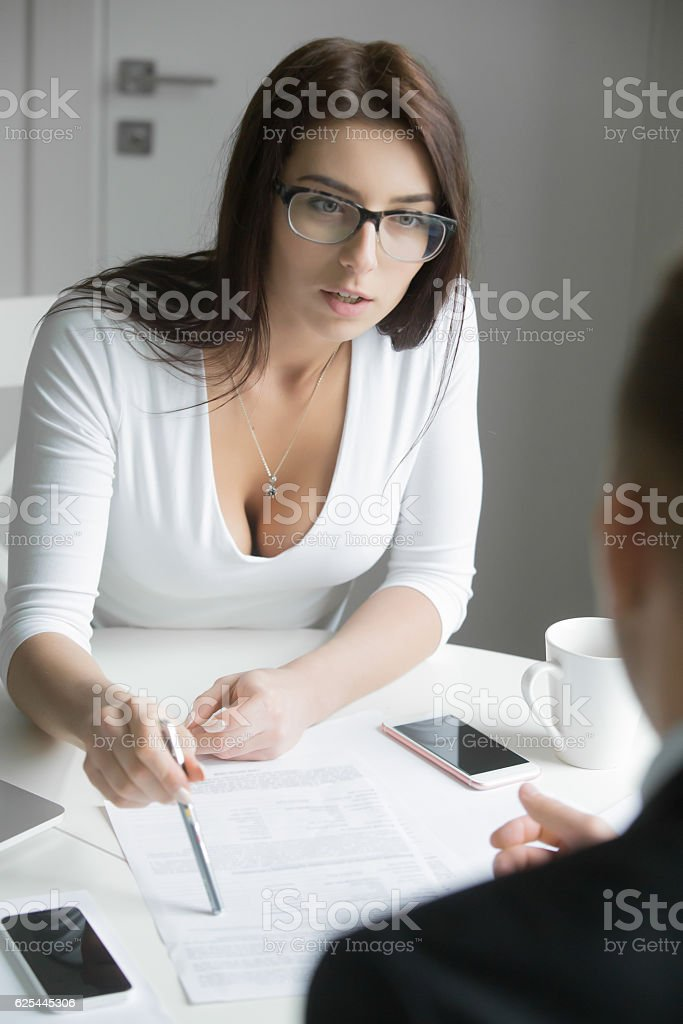 Young businesswoman pointing to a paper with a pen stock photo