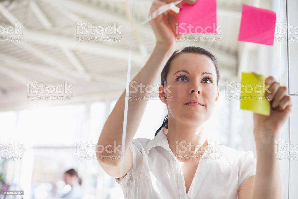 Jovem Empresária a aplicação Notas de adesivos na parede de vidro do escritório - fotografia de stock