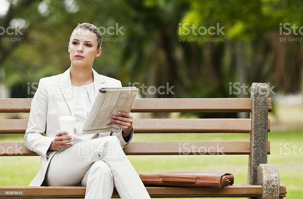 Young Businesswoman Reading a Newspaper in the Park royalty-free stock photo
