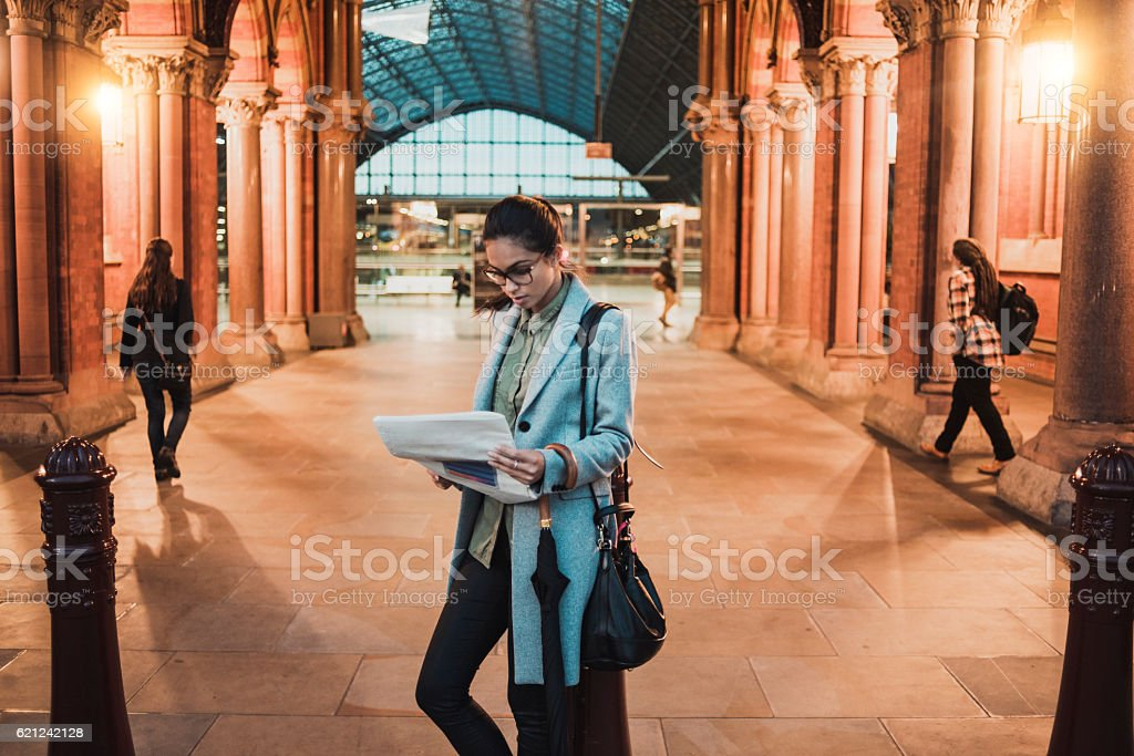 young businesswoman reading newspaper on the station stock photo
