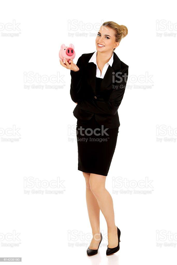 Young businesswoman saving money in piggybank stock photo