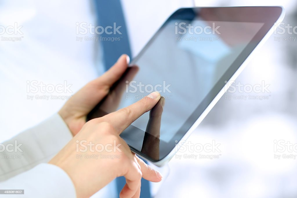Young businesswoman showing graphs by finger at the digital tablet stock photo