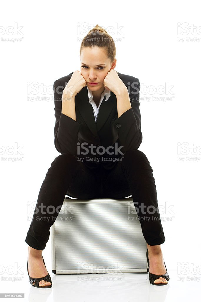Young businesswoman sitting on a briefcase royalty-free stock photo