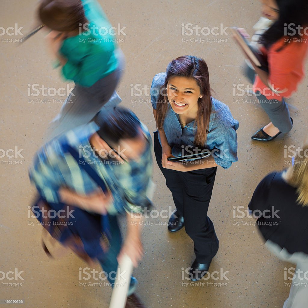 Young businesswoman smiling as crowd moves past her quickly stock photo