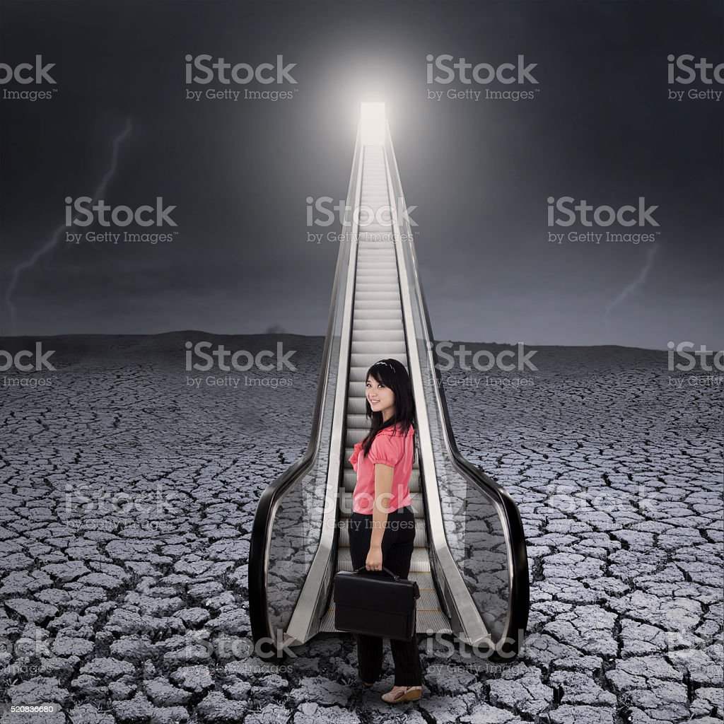 Young businesswoman standing by the escalator stock photo