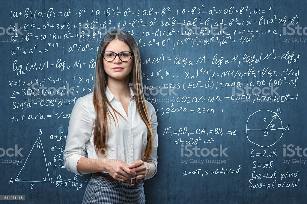 Young businesswoman standing on the background of blackboard with mathematical stock photo