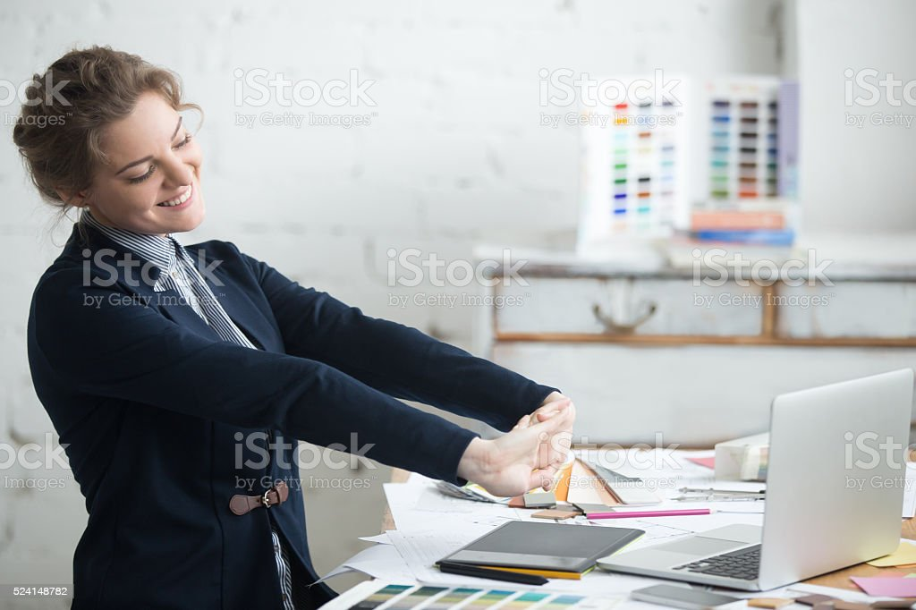Young businesswoman stretching after work stock photo