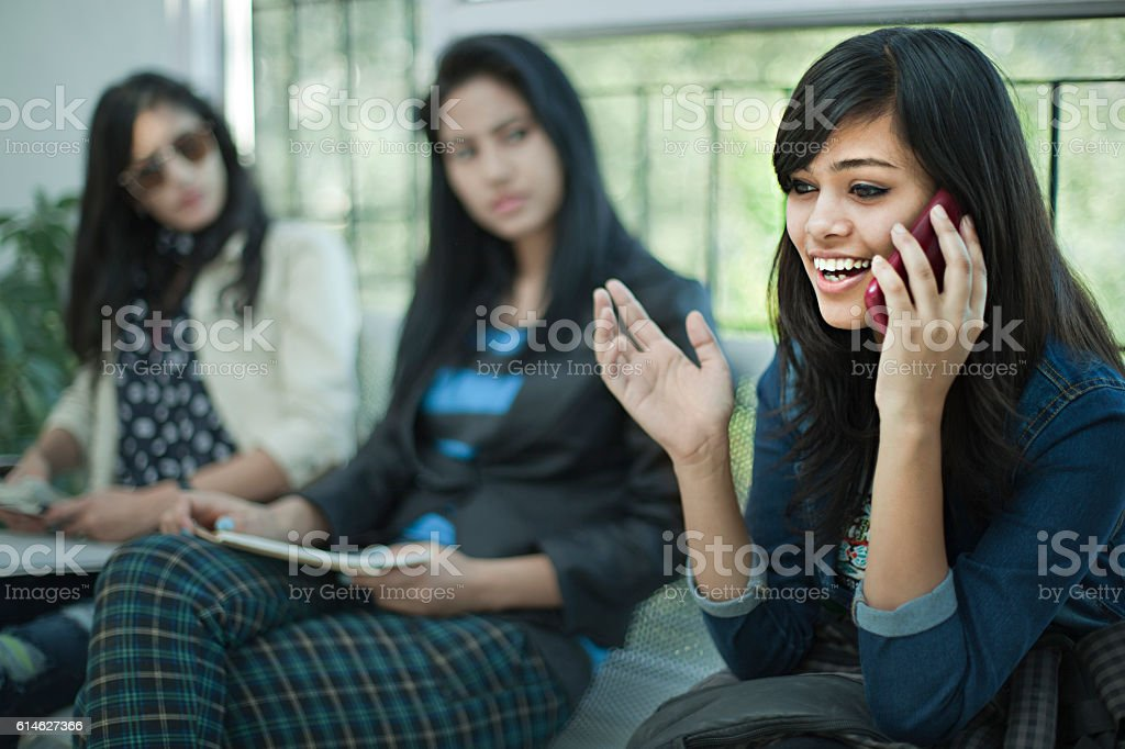 Young businesswoman talking loud on phone in office waiting room. stock photo