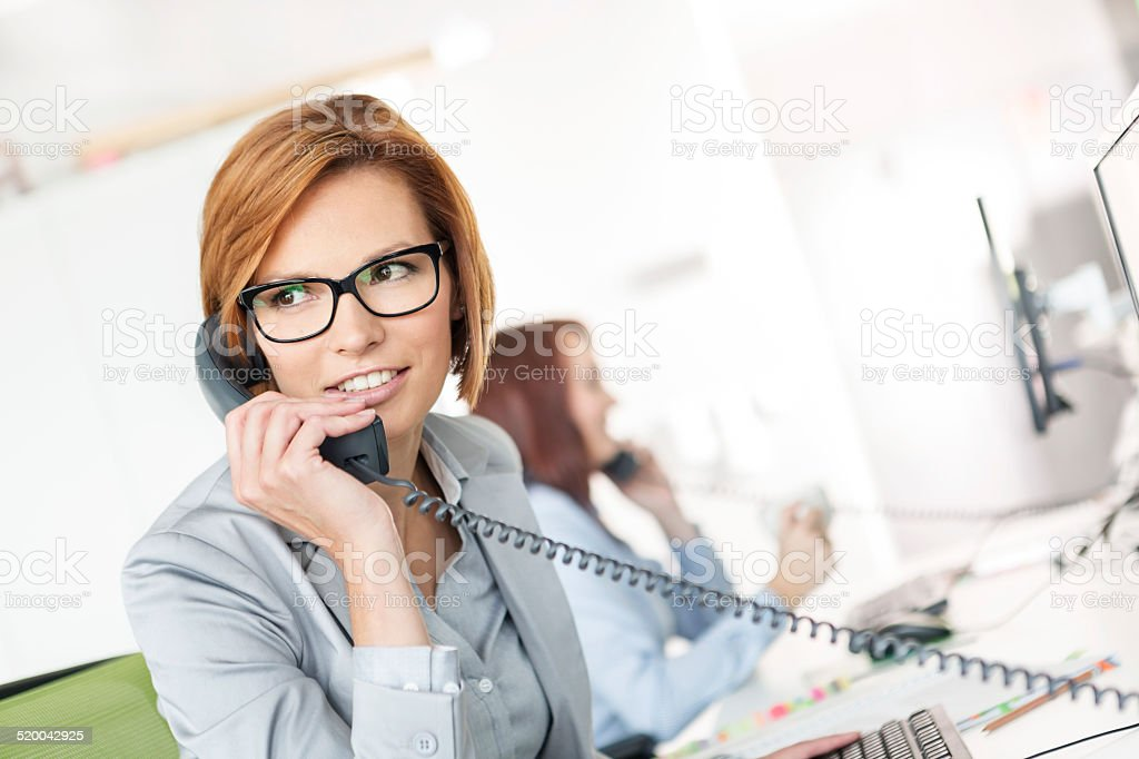 Young businesswoman talking on telephone at desk in office stock photo