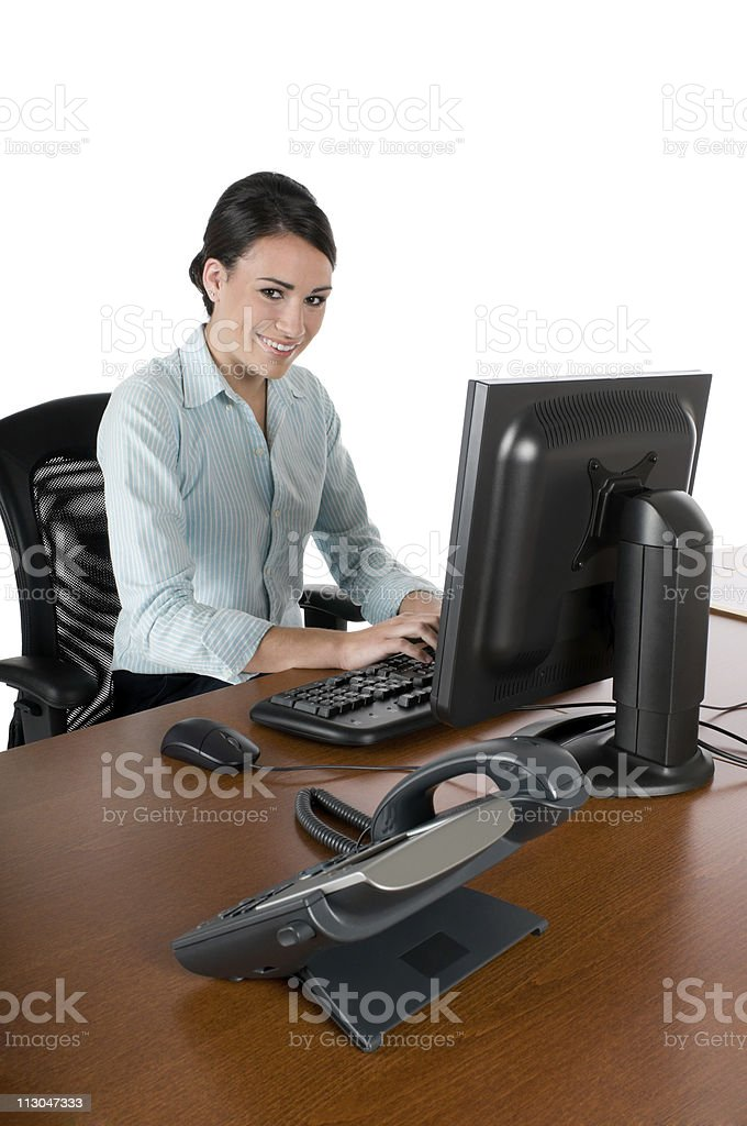 Young businesswoman typing at computer, isolated on white royalty-free stock photo