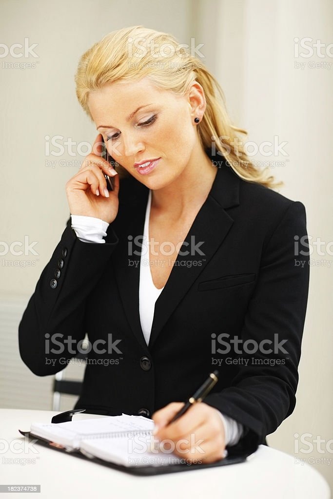 Young businesswoman using cellphone and making notes royalty-free stock photo