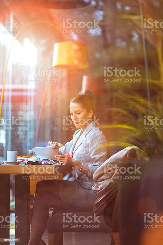 Young businesswoman using her digital tablet at restaurant stock photo
