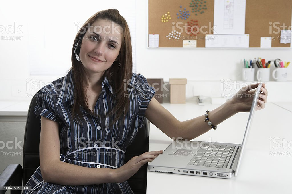 Young businesswoman using laptop in office, smiling, portrait stock photo