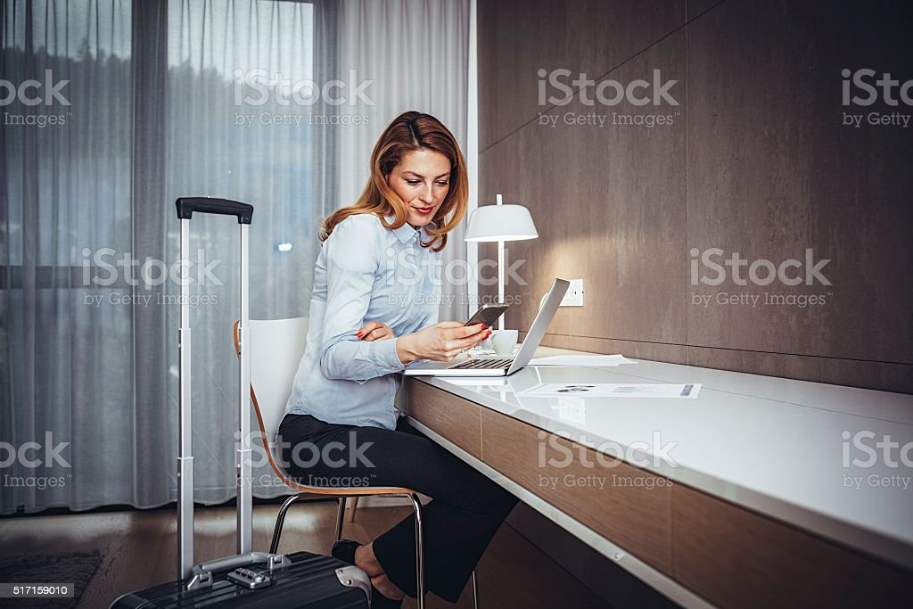 Young businesswoman using mobile  phone  in hotel room stock photo