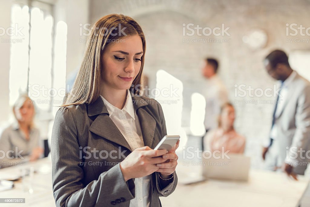 Young businesswoman using smart phone in the office. stock photo