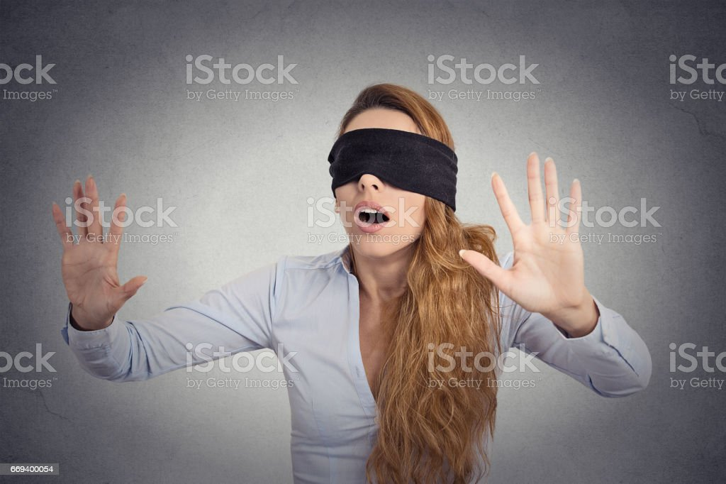 Young businesswoman walking blindfolded with hands forward isolated on grey wall background stock photo