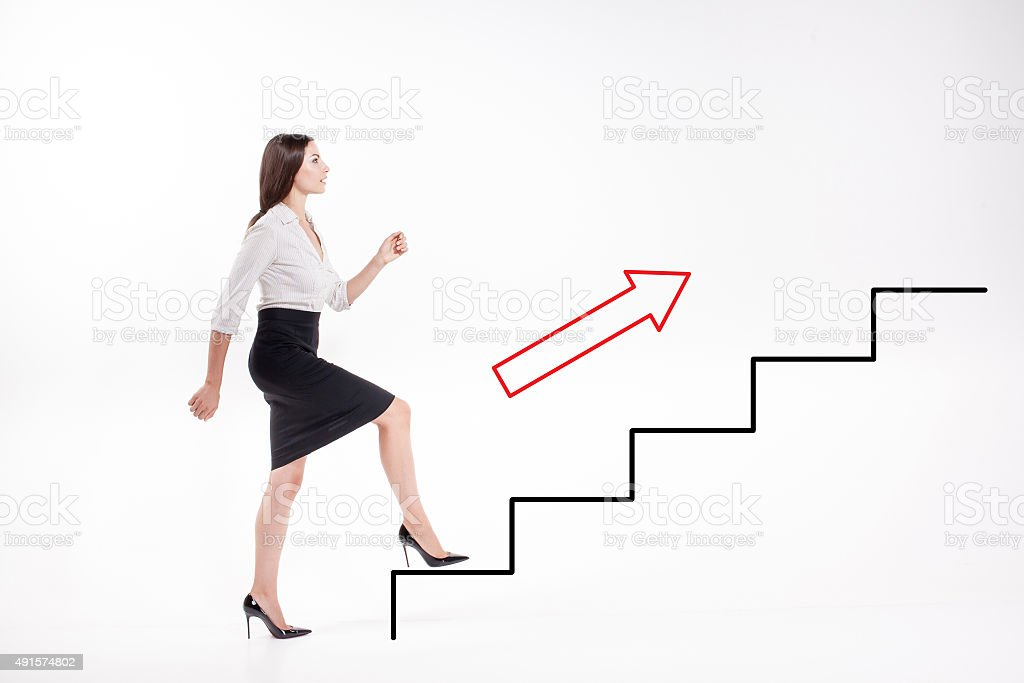 Young businesswoman walking up on stairs stock photo