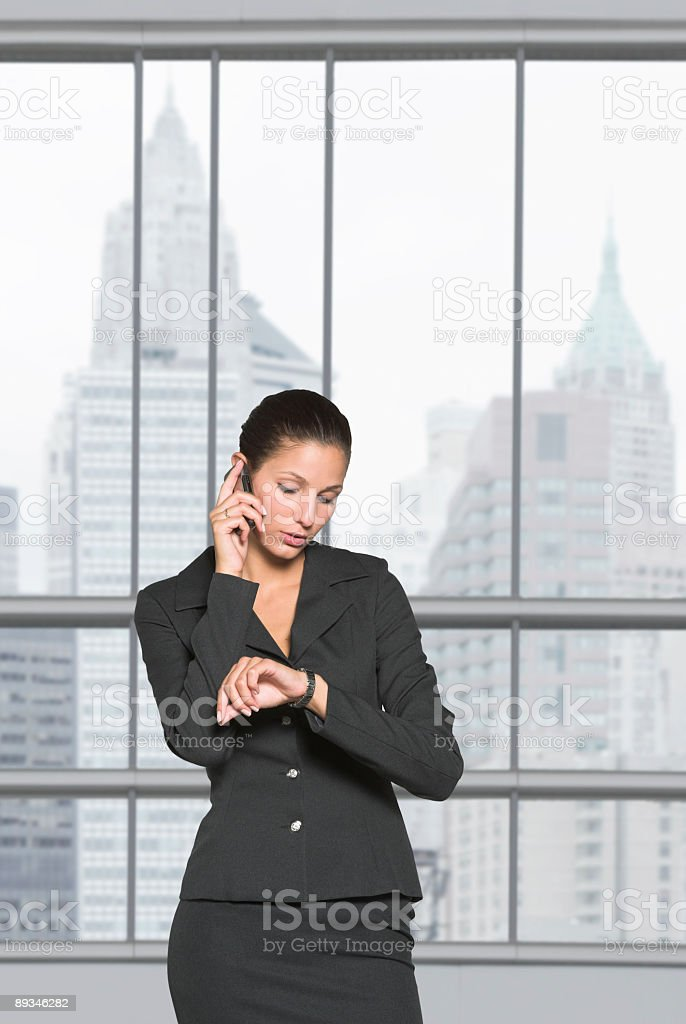 Young businesswoman watching her clock royalty-free stock photo