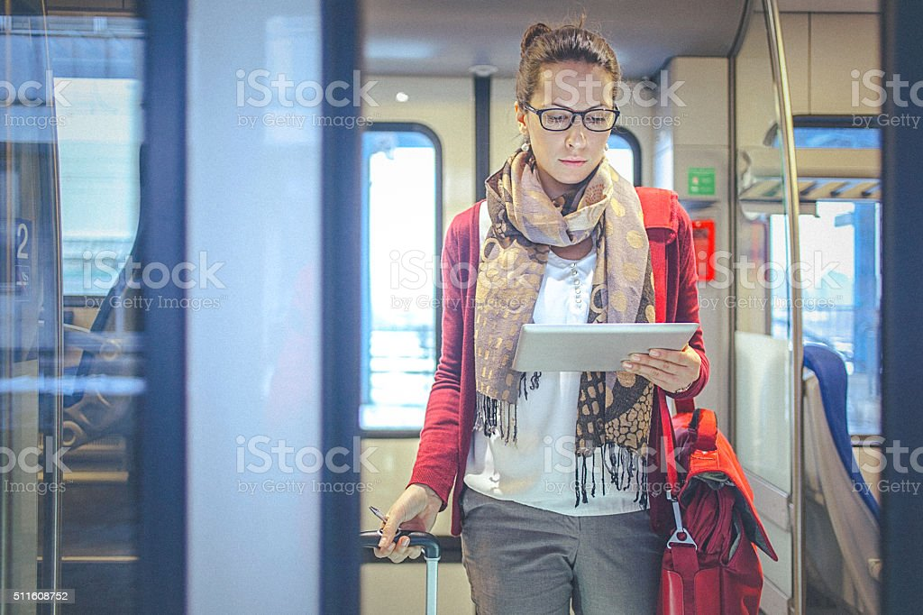 Young businesswoman watching tablet while commuting to work by train stock photo
