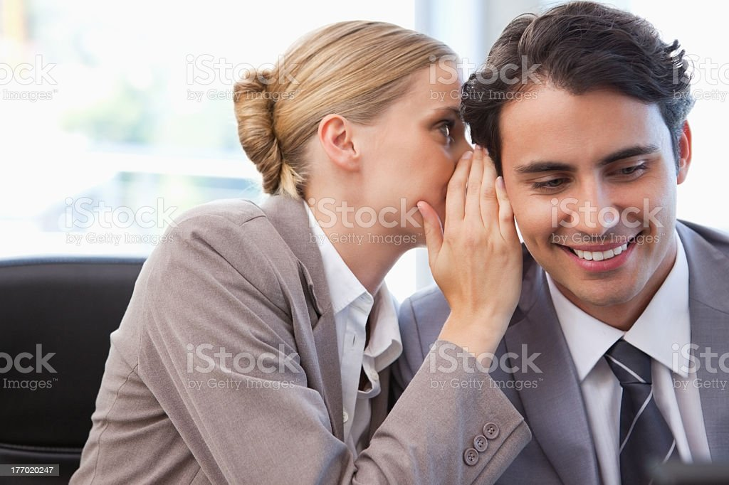 Young businesswoman whispering something to her colleague stock photo