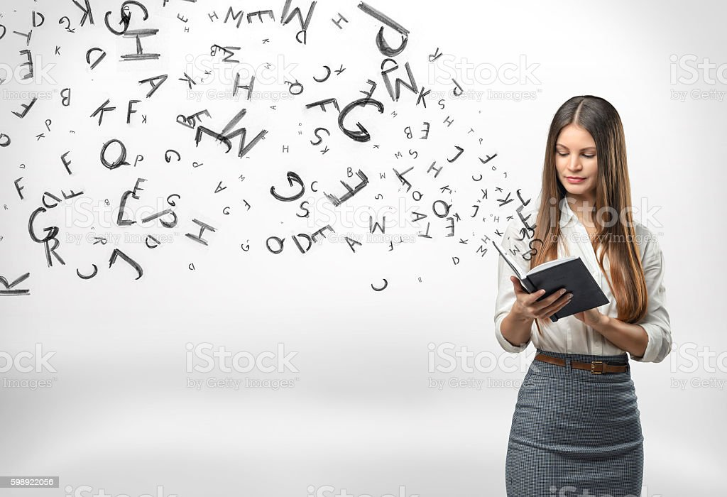 Young businesswoman with a notebook and letters flying out of stock photo