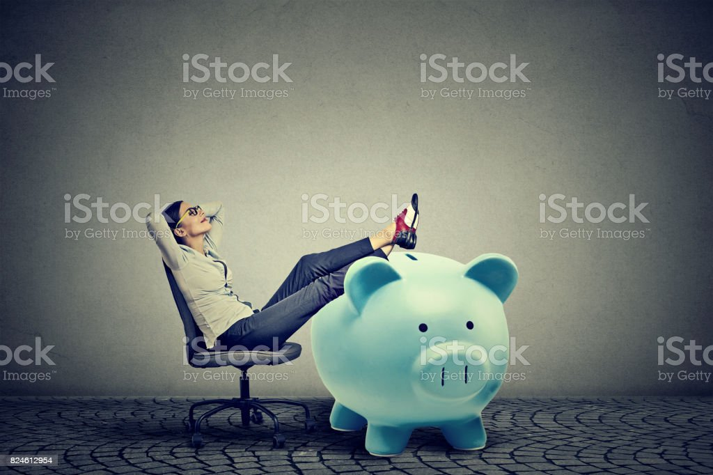 young businesswoman with big piggy bank relaxing sitting on chair stock photo