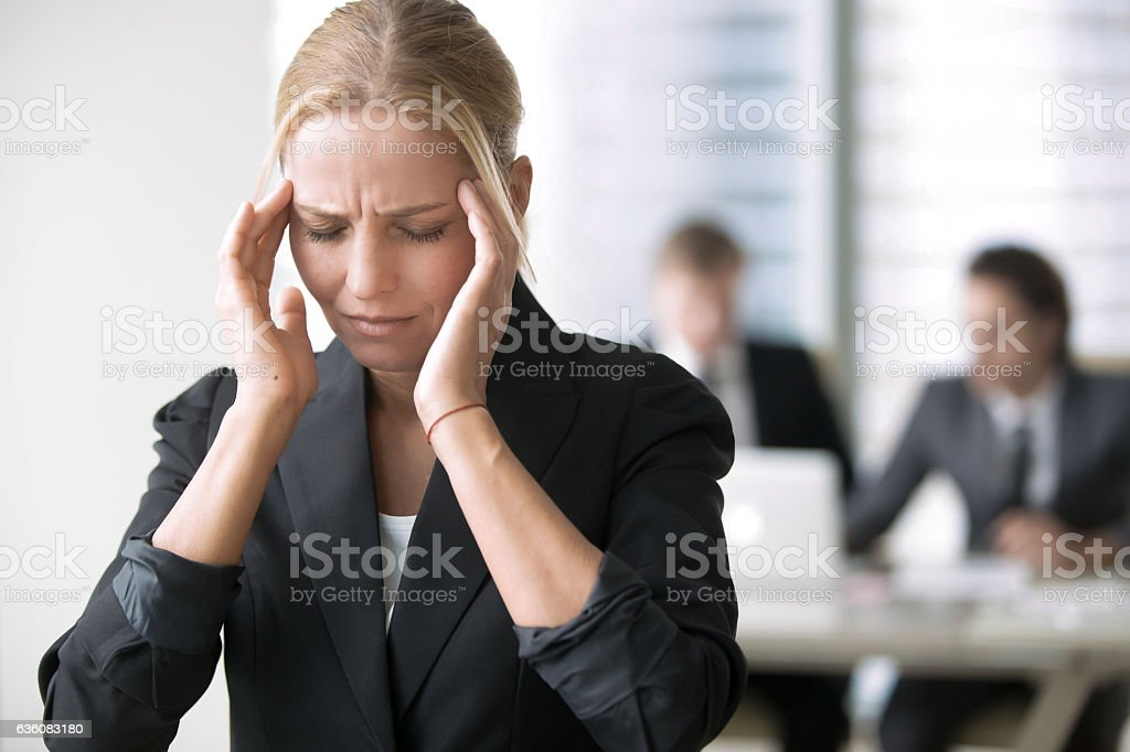 Young businesswoman with headache stock photo