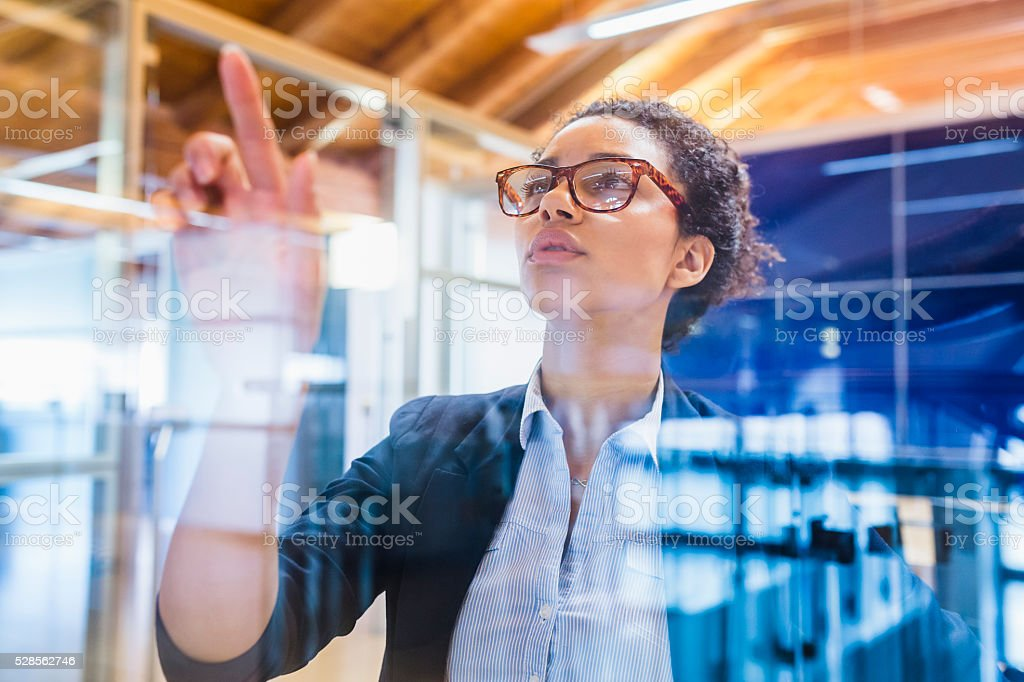 Young businesswoman with index finger on window panel stock photo
