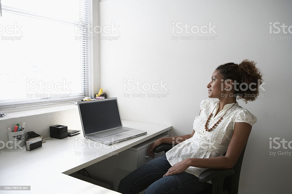 Young businesswoman with laptop sitting at desk, looking out window stock photo