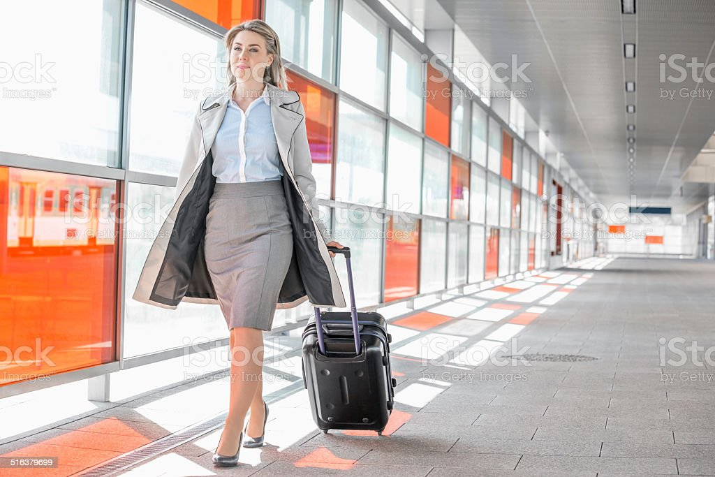 Young businesswoman with luggage walking in railroad station stock photo