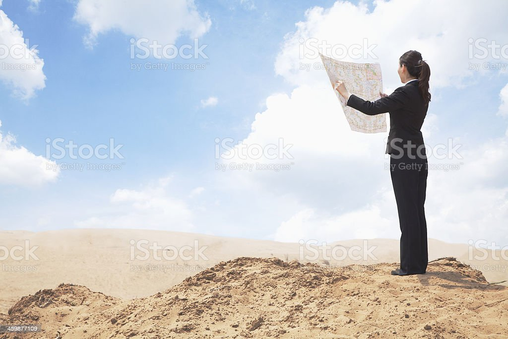 Young businesswoman with map in middle of desert stock photo