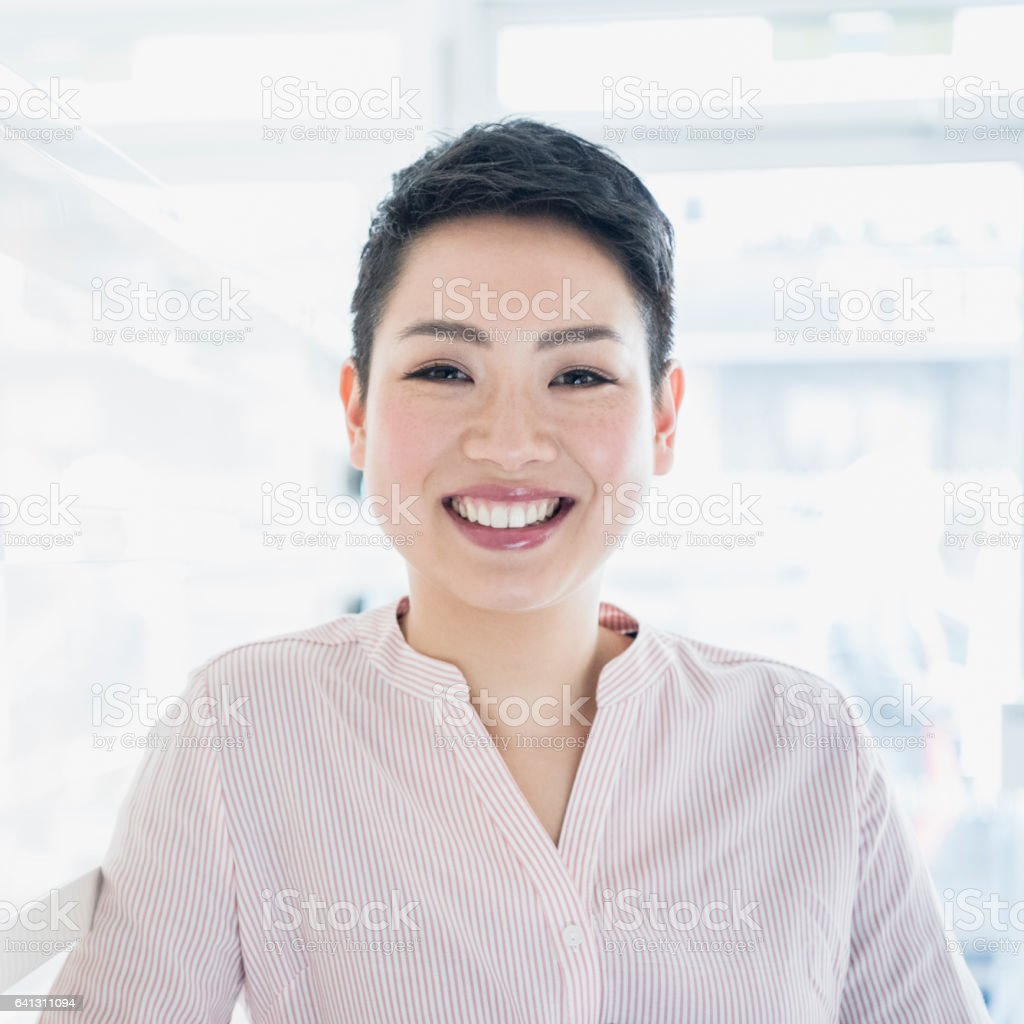 Young businesswoman with short hair smiling towards camera stock photo