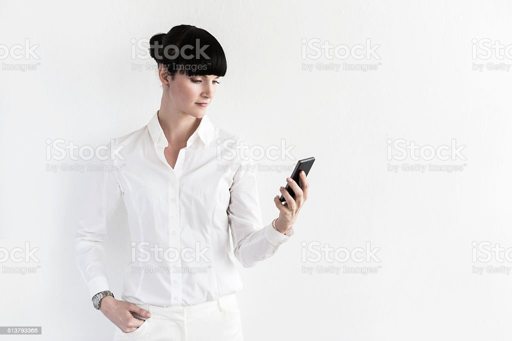 Young Businesswoman With Smartphone At A White Wall stock photo
